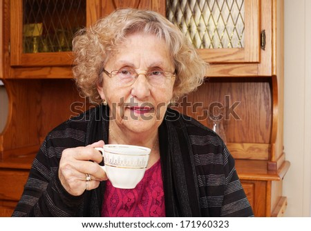 Happy senior woman drinking tea at home - stock photo