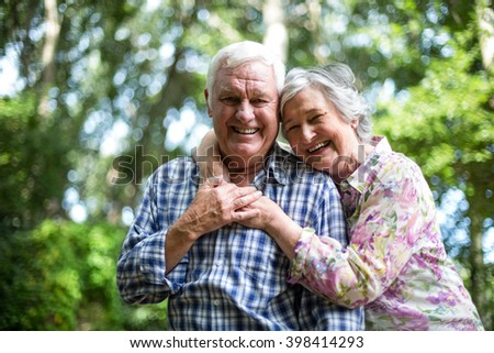 Happy senior woman embracing from behind husband against trees in back yard - stock photo