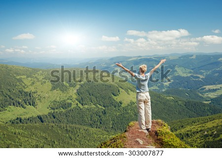 Happy senior woman enjoying the nature in the mountains and looking on sky with raised hands. Freedom concept - stock photo