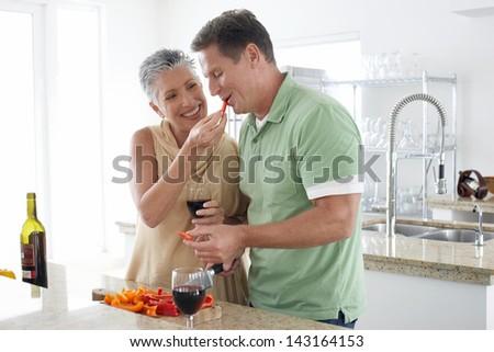 Happy senior woman feeding pepper to man in kitchen - stock photo