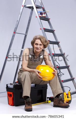 Happy senior woman holding a safety hat sitting in a toolbox - stock photo