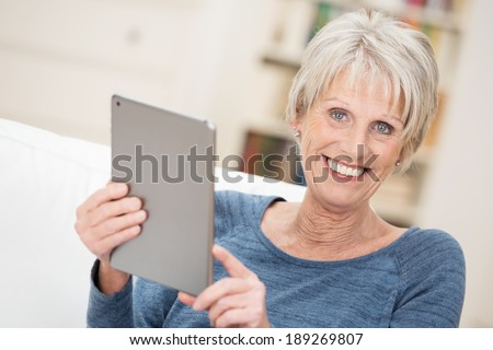 Happy senior woman holding a tablet computer in her hands as she relaxes on a sofa in the living room looking at the camera with a warm beaming smile - stock photo