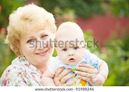 Happy senior woman holding baby boy in spring flowery garden. Nature green blurred background - stock photo
