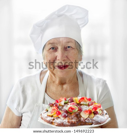 Happy Senior woman holding plate pie with fruits - stock photo