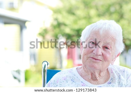 Happy Senior Woman in a Wheelchair Outside - stock photo