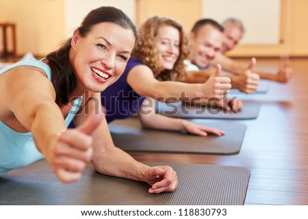 Happy senior woman in fitness class in a health club holding her thumbs up - stock photo