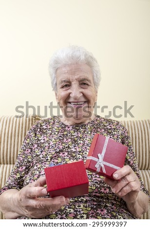 happy senior woman opening a gift box - stock photo