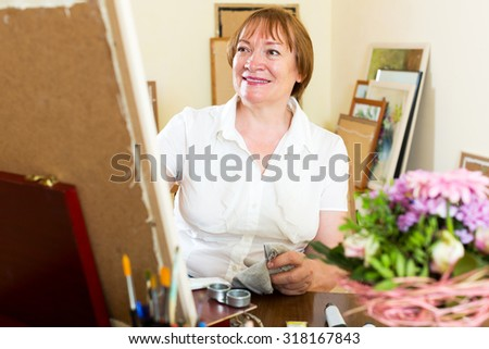 Happy senior woman painting a new picture - stock photo