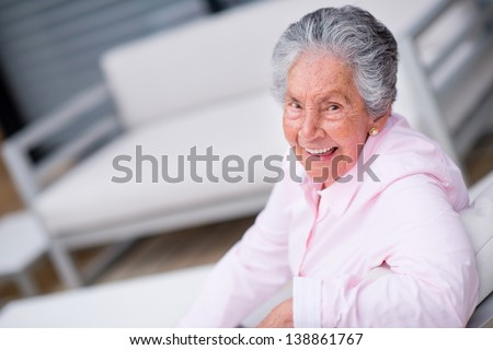 Happy senior woman relaxing at home and smiling - stock photo