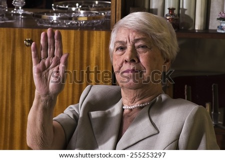 Happy senior woman sitting at home and relaxing. - stock photo