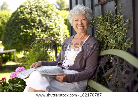 Happy senior woman sitting on bench in her backyard garden with a newspaper looking at camera smiling - stock photo