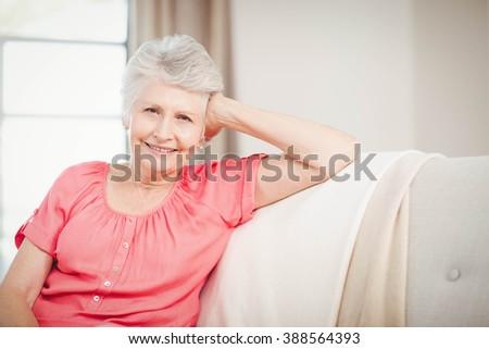 Happy senior woman sitting on sofa in living room - stock photo