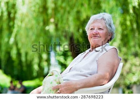 Happy senior woman sitting outside - stock photo