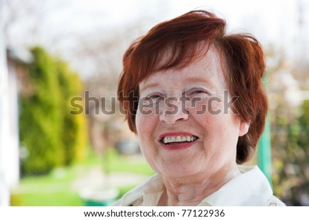 Happy senior woman smiling outdoor - stock photo