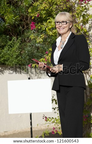 Happy senior woman standing by sign board with clipboard - stock photo