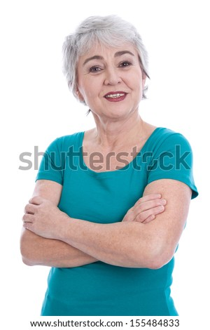 Happy senior woman standing with arms crossed - stock photo