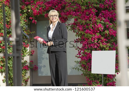 Happy senior woman standing with clipboard - stock photo