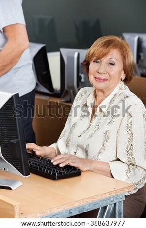 Happy Senior Woman Using Computer At Desk In Classroom - stock photo