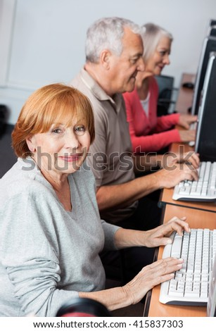 Happy Senior Woman Using Computer In Classroom - stock photo