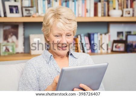 Happy senior woman using digital tablet at home - stock photo