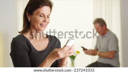 Happy senior woman using smartphone - stock photo