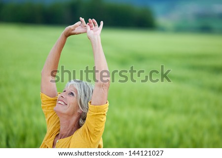 Happy senior woman with arms raised looking up while standing on grassy field - stock photo