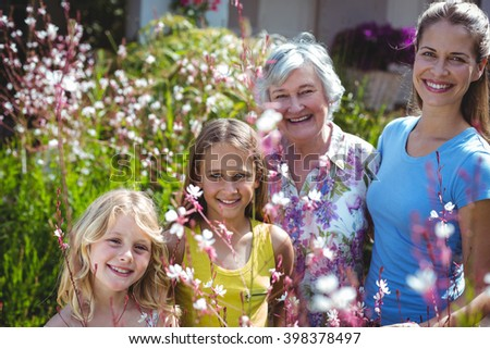 Happy senior woman with daughter and girls in back yard during sunny day - stock photo