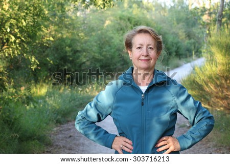 Happy senior woman with hands around the waist hiking in the woods - stock photo