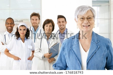 Happy senior woman with medical team in background. - stock photo