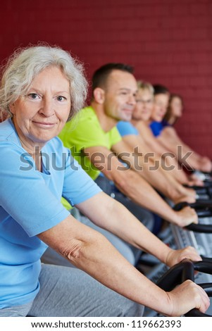 Happy senior woman with other people in spinning class in health club - stock photo