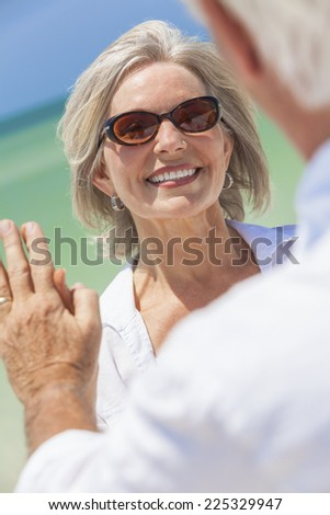 Happy senior woman with perfect teeth dancing with man in a couple and holding hands on a deserted tropical beach with bright clear blue sky - stock photo
