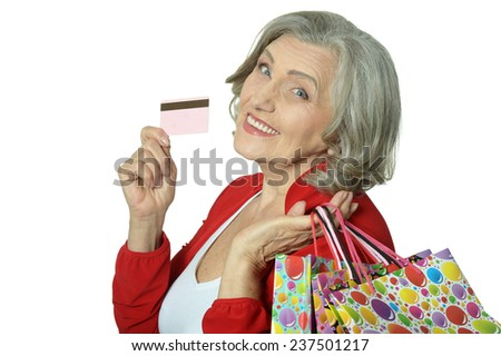 Happy senior woman with shopping bags and credit card - stock photo