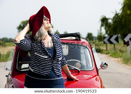 Happy senior woman with vintage car - stock photo