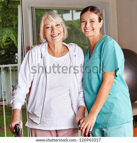 Happy senior woman with walker and nurse in a physiotherapy - stock photo