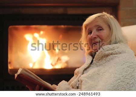 Happy senior woman, wrapped in warm knitted plaid, relaxing at home in the evening, sitting in rocking chair by fireplace and reading a book - successful retirement concept - stock photo