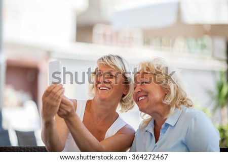 Happy senior women making mobile selfie - stock photo