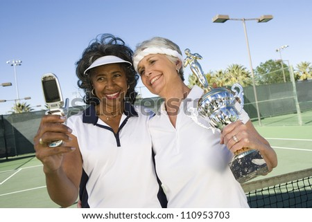 Happy senior women with trophy taking self-portrait through cell phone on tennis court - stock photo