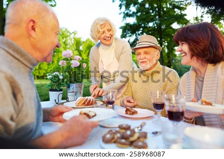 Happy seniors at birthday party sitting with cake in the garden - stock photo