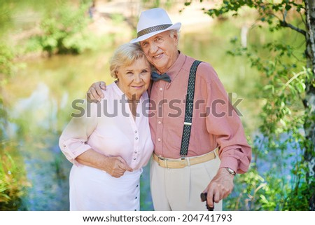Happy seniors in smart casual looking at camera in park - stock photo