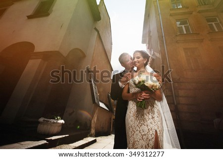 Happy sensual brunette bride with hugging outdoors with groom in sunlit street - stock photo