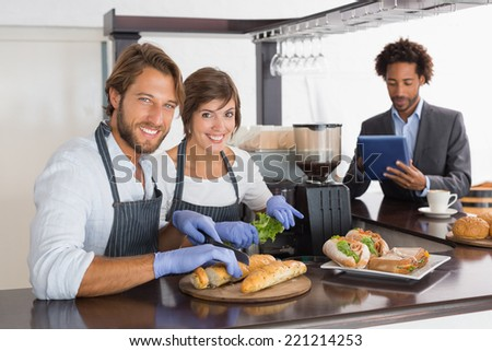 Happy servers preparing sandwiches together at the coffee shop - stock photo