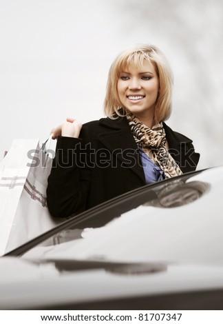 Happy shopper on a car parking - stock photo