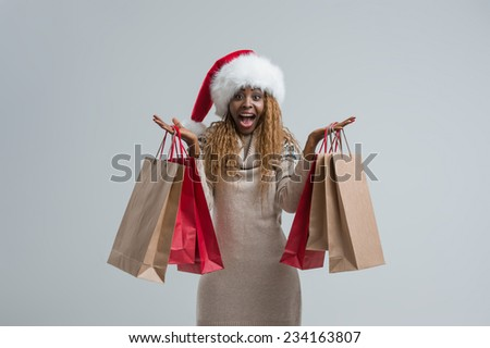 Happy shopping Christmas woman wearing Santa Claus hat with bags gray background - stock photo