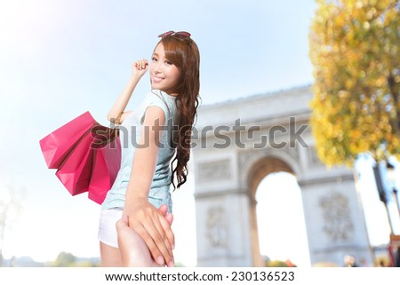 Happy Shopping in Paris - beautiful young woman holding colored shopping bags with Arc de Triomphe - stock photo