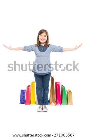 Happy shopping kid or young girl standing with shopping bags on white background - stock photo