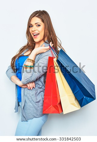 Happy shopping woman holding paper bag. Smiling girl portrait on white background. Young female model one in studio. - stock photo