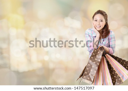 Happy shopping woman of Asian holding bags at a mall. - stock photo