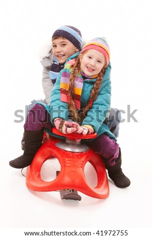 Happy siblings looking at camera while sitting on sledge - stock photo