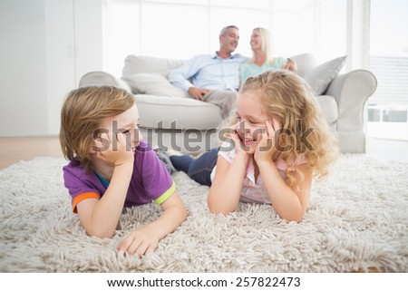 Happy siblings looking at each other while parents sitting on sofa at home - stock photo