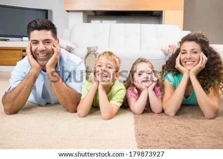 Happy siblings lying on the rug posing with their parents at home in living room - stock photo